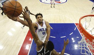 Philadelphia 76ers' Jahlil Okafor (8) goes up for the shot with Brooklyn Nets' Thaddeus Young (30) defending during the second half of an NBA basketball game, Saturday, Feb. 6, 2016, in Philadelphia. The 76ers won 103-98. (AP Photo/Chris Szagola)