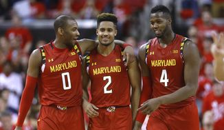Maryland guard Rasheed Sulaimon, guard Melo Trimble and forward Robert Carter, from left, celebrate in the final moments of the team's NCAA college basketball game against Purdue, Saturday, Feb. 6, 2016, in College Park, Md. The three contributed a combined 54 points to Maryland's 72-61 win. (AP Photo/Patrick Semansky)