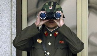A North Korean soldier looks at the southern side through a pair of binoculars at the border village of Panmunjom, which has separated the two Koreas since the Korean War, in Paju, north of Seoul, South Korea, on April 23, 2013. (Associated Press)