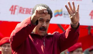 Venezuela's President Nicolas Maduro signals the date of a failed coup led by late President Hugo Chavez during a parade marking its anniversary in Caracas, Venezuela. (AP Photo/Ariana Cubillos)