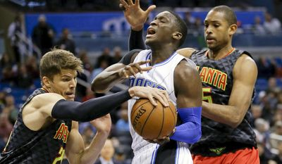 Atlanta Hawks guard Kyle Korver, left, and center Al Horford, right, strip the ball from Orlando Magic guard Victor Oladipo, center, during the first half of an NBA basketball game, Sunday, Feb. 7, 2016, in Orlando, Fla. (AP Photo/John Raoux)
