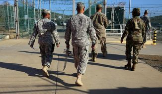 In this Feb. 2, 2016 photo, military guards exit an area known as Camp Delta at the Guantanamo Bay detention center, in Cuba. After 14 years, the detention center appears to be winding down despite opposition in Congress to President Barack Obama's intent to close the facility and confine the remaining prisoners someplace else. (AP Photo/Ben Fox)