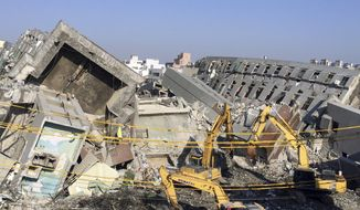 Rescue workers using excavators continue to search the rubble of a collapsed building complex in Tainan, Taiwan, Tuesday, Feb. 9, 2016. (AP Photo/Annie Ho)