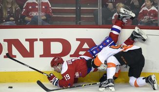 Washington Capitals center Nicklas Backstrom (19), of Sweden, is upended as he battles for the puck against Philadelphia Flyers center Nick Cousins, right, during the third period of an NHL hockey game, Sunday, Feb. 7, 2016, in Washington. (AP Photo/Nick Wass)