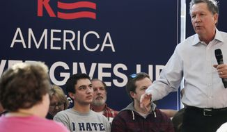 Alex Tsipis of Wayland, Mass., left, listens to Republican presidential candidate, Ohio Gov. John Kasich during a campaign stop in Nashua, N.H., Sunday, Feb. 7, 2016.  Tipis travelled New Hampshire to hear Kasich in person. (AP Photo/Charles Krupa)