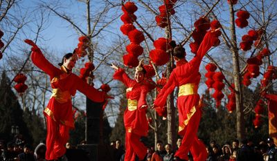 Chinese dancers dressed in traditional costumes perform a cultural dance on stage during a temple fair for a Lunar New Year celebration in Beijing, Monday, Feb. 8, 2016. Millions of Chinese began celebrating the Lunar New Year, which marks the Year of the Monkey on the Chinese zodiac. (AP Photo/Andy Wong)