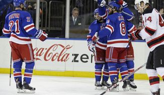 New York Rangers Kevin Klein (8) is congratulated by teammates after scoring a goal against the New Jersey Devils in the second period of an NHL hockey game Monday, Feb. 8, 2016, in New York. (AP Photo/Adam Hunger)