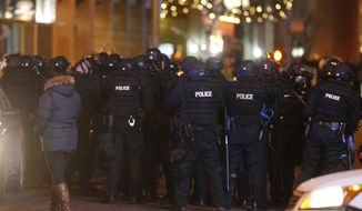 Denver Police Department officers in riot gear prepare to stand down a cadre of Denver Broncos fans as they celebrate the team's victory over the Carolina Panthers in Super Bowl 50 late Sunday, Feb. 7, 2016, in Denver. (AP Photo/David Zalubowski)