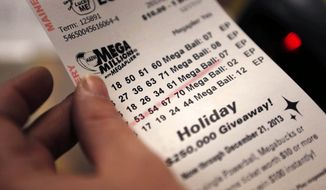 A cashier holds a Mega Millions lottery ticket at a convenience store in Lisbon, Maine. (Associated Press)