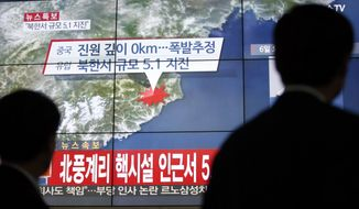 In this Wednesday, Jan. 6, 2016, file photo, people walk by a screen showing the news reporting about an earthquake near North Korea's nuclear facility, in Seoul, South Korea. (AP Photo/Lee Jin-man, File)
