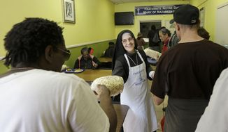 Sister Mary Valerie, center, hands out bags of popcorn at the Fraternite Notre Dame Mary of Nazareth Soup Kitchen in San Francisco, Tuesday, Feb. 9, 2016. SanFrancisco nuns who serve the homeless are in danger of getting kicked out of their home after a rent hike of more than 50 percent. (AP Photo/Jeff Chiu)