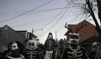 The North Side Skull & Bone Gang parade down the streets during the wake up call for Mardi Gras, Tuesday, Feb. 9, 2016, in New Orleans. Their costumes are intended to represent the dead and they bring a serious message, reminding people of their mortality and the need to live a productive and good life. (AP Photo/Brynn Anderson)