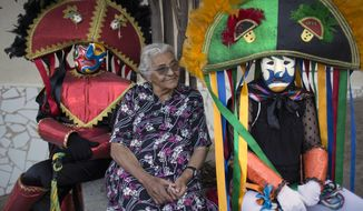 """Caretas"" performers sit next to an elderly woman during Carnival celebrations in Triunfo, Brazil, Monday, Feb. 8, 2016. Revelers take to the streets in hand-made costumes that feature huge hats, long whips _ and scowling masks.  (AP Photo/Felipe Dana)"