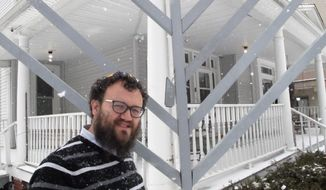 Rabbi Dovid Tiechtel poses near the damaged menorah outside the Chabad Center at the University of Illinois in Champaign, Ill., on Tuesday, Feb. 9, 2016. The menorah has been damaged three times in less than a year, most recently on Feb. 7. (AP Photo/David Mercer)