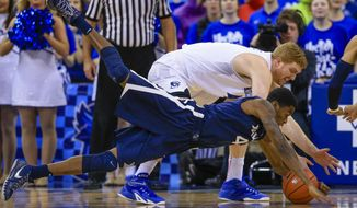 Xavier's Edmond Sumner (4) and Creighton's Geoffrey Groselle, rear, scramble for a loose ball during the first half of an NCAA college basketball game in Omaha, Neb., Tuesday, Feb. 9, 2016. (AP Photo/Nati Harnik)