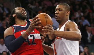 New York Knicks center Kevin Seraphin (1) fouls Washington Wizards center Nene Hilario (42) in the first half of an NBA basketball game at Madison Square Garden in New York, Tuesday, Feb. 9, 2016. (AP Photo/Kathy Willens)