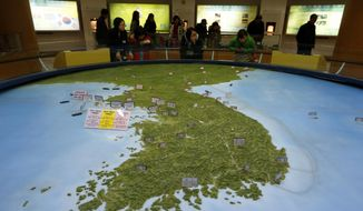 Visitors look at a map of the Korean peninsula at the exhibition hall of the unification observatory in Paju, South Korea, Wednesday, Feb. 10, 2016. South Korea says it will suspend the operations at a joint industrial park with North Korea in response to the North's recent rocket launch.  (AP Photo/Lee Jin-man) ** FILE **