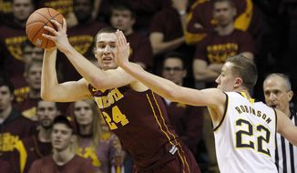 Minnesota forward Joey King (24) looks to pass to a teammate under pressure from Michigan guard Duncan Robinson (22) during the first half of an NCAA college basketball game in Minneapolis, Wednesday, Feb. 10, 2016. (AP Photo/Ann Heisenfelt)