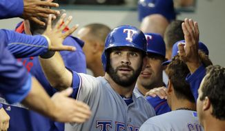 FILE - In this Sept. 8, 2015, file photo, Texas Rangers' Mitch Moreland, center, is greeted in the dugout after he hit a solo home run during the second inning of a baseball game against the Seattle Mariners, in Seattle. Moreland has agreed to a $5.7 million, one-year contract with the Texas Rangers, avoiding a salary arbitration hearing set for later Wednesday, Feb. 10, 2016. (AP Photo/Ted S. Warren, File)