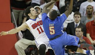 SMU guard Nic Moore (11) defends the basket against Tulsa guard Rashad Ray (5) during the first half of an NCAA college basketball game Wednesday, Feb. 10, 2016, in Dallas. (AP Photo/LM Otero)
