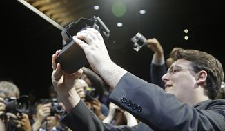 FILE - In this June 11, 2015 file photo, Oculus founder Palmer Luckey holds up the new Oculus Rift virtual reality headset for photographers following a news conference, in San Francisco. Luckey and other pioneers of modern virtual reality technology from such companies as Google and Sony are gathering for a summit on Wednesday, Feb. 10, 2016, about the immersive medium in Hollywood. (AP Photo/Eric Risberg, File)