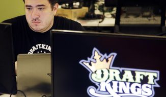 FILE - In this Sept. 9, 2015 file photo, Len Don Diego, marketing manager for content at the DraftKings daily fantasy sports company, works at his station at the company's offices in Boston. Daily fantasy sports companies have said their industry remains viable despite a rocky start to 2016.  ESPN and DraftKings ended an exclusive advertising deal, and FanDuel confirmed it was laying off 55 workers in its Orlando, Fla., office. (AP Photo/Stephan Savoia, File)