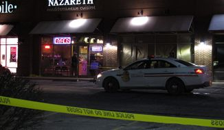 Police talk inside the Columbus, Ohio, restaurant where they say a man attacked several people with a machete on Thursday, Feb. 11, 2016. They say the man fled the scene and was later fatally shot by police. (AP Photo/Kantele Franko)