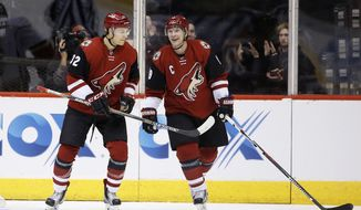 Arizona Coyotes' Shane Doan, right, celebrates his goal against the Calgary Flames with teammate Tyler Gaudet (32) during the first period of an NHL hockey game Friday, Feb. 12, 2016, in Glendale, Ariz. (AP Photo/Ross D. Franklin)