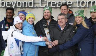 International Olympic Committee President Thomas Bach, 3rd right, front row, poses for the medida with the torch of the Lillehammer 2016 Winter Youth Olympic Games with Olympic Gold medalist Kjetil Jansrud of Norway, center, and young ambassadors and volunteers of the games, in Lillehammer, Norway, Friday Feb. 12, 2016. (Jed Leicester/IOC via AP)