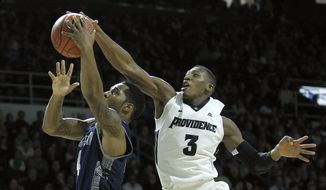 Providence guard Kris Dunn (3) blocks a shot by Georgetown guard D'Vauntes Smith-Rivera (4) during the second half of an NCAA college basketball game in Providence, R.I., Saturday, Feb. 13, 2016. (AP Photo/Stew Milne)