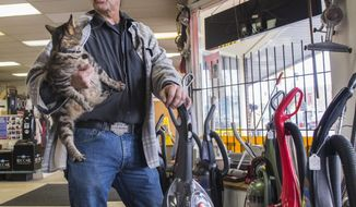 In this Feb. 5, 2016 photo, Tom Pruett, manager of Big Vac Inc., holds a cat as he talks about the return of the Lunar New Year celebration and a planned revitalization of the Lincoln District that he hopes will attract more customers to his family's business, in Tacoma, Wash. (Drew Perine/The News Tribune via AP)