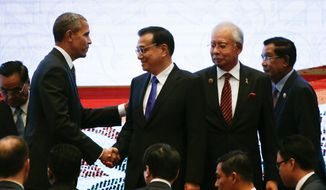 In this Nov. 22, 2015, file photo, U.S. President Barack Obama, left, shakes hands with Chinese Premier Li Keqiang, second left, while Malaysian Prime Minister Najib Razak, second right, and Laotian Prime Minister Thongsing Thammavong look on during the 10th East Asia Summit at the 27th ASEAN Summit in Kuala Lumpur, Malaysia. (AP Photo/Vincent Thian, File)