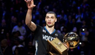 Minnesota Timberwolves' Zach LaVine holds the trophy after winning the slam dunk contest during the NBA basketball All-Star weekend in Toronto, Saturday, Feb. 13, 2016. (Mark Blinch/The Canadian Press via AP)