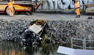 A badly damaged car is towed up from the canal under the E4 highway bridge in Sodertalje, Sweden, Saturday, Feb.13, 2016. Swedish police say five people have been killed when their car plunged more than 25 meters (82 feet) from a highway bridge into a canal in the capital of Stockholm. (Johan Nilsson/TT News Agency via AP) SWEDEN OUT