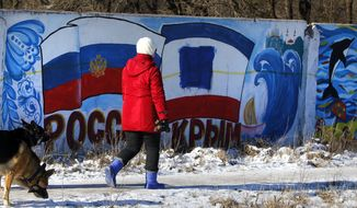 In this Monday, Jan. 25, 2016, file photo, a woman walks with her dog past a graffiti depicting the Russia and Crimean flags on the outskirts of Simferopol, Crimea. Two years after Russia seized Crimea from Ukraine, President Vladimir Putin touts the move as a historic achievement, looking on with a satisfied smile from countless billboards across the peninsula. However, overwhelming opposition from the Muslim Tatar ethnic minority puts a crack in this picture of unanimous support, as evidenced in interviews with more than two dozen Tatars across Crimea. And the resistance appears to be growing. (AP Photo/Sergei Grits)