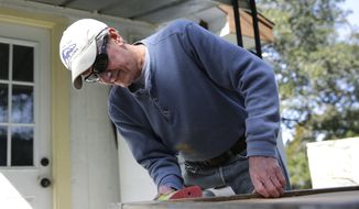 Walt Whitlow uses a powers sander on a project at his home, Monday, Feb. 8, 2016, in Leander, Texas. Whitlow was undergoing cancer treatment when he learned his premiums for coverage under President Barack Obama's health care law quadrupled and his deductible went from $900 to $4,600. (AP Photo/Eric Gay)
