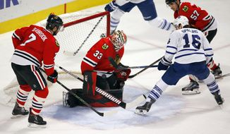 Chicago Blackhawks goalie Scott Darling (33) stops the shot of Toronto Maple Leafs center Nick Spaling (16) during the second period of an NHL hockey game Monday, Feb. 15, 2016, in Chicago. (AP Photo/Jeff Haynes)