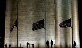 Visitors are silhouetted as flags fly at half-staff around the base of the Washington Monument in Washington, Tuesday, Feb. 16, 2016, in honor of Supreme Court Justice Antonin Scalia who died over the weekend at age 79.  (AP Photo/Carolyn Kaster)