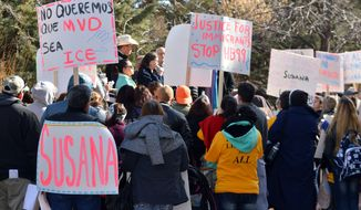 FILE - In this Jan. 25, 2016 file photo, immigrant advocates hold a rally outside the New Mexico statehouse to voice their opposition to a GOP-sponsored proposal that would make New Mexico REAL ID compliant by ending the practice of granting driver's licenses to immigrants in the country illegally. New Mexico Gov. Susana Martinez finally got lawmakers to pass her long-sought revision of a state law that grants driver's licenses to immigrants in the country illegally. (AP Photo/Russell Contreras)