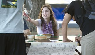 This Monday, Feb. 15, 2016, Texas A&M student Hope Beitchman, a member of Texas A&M Hillel, takes letters from students passing by her station set up for that purpose in Rudder Plaza in College Station, Texas. Texas A&M University System Chancellor John Sharp apologized Tuesday to high school students for racial insults that some minority students say they heard while visiting the College Station campus last week. (Dave McDermand/College Station Eagle via AP)