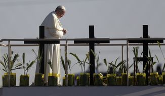 Pope Francis stands on a praying platform on the banks of the Rio Grande in Juarez, Mexico, as he prays for a group of migrants sitting along the border fence in El Paso, Texas, Wednesday, Feb. 17, 2016. Pope Francis offered a prayer for the migrants who have died crossing the border. (AP Photo/Eric Gay)