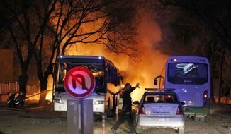 A police officer clears the area of an explosion in Ankara, Wednesday, Feb. 17, 2016, after assailants exploded a car bomb near vehicles carrying military personnel in the Turkish capital, killing several people and injuring scores of others, officials said. The explosion occurred during evening rush hour in the heart of city, in an area close to where military headquarters and the parliament are located. (Mustafa Kirazli/Cihan News Agency via AP)