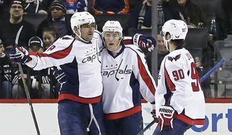 Washington Capitals' Alex Ovechkin, left, celebrates with teammates T.J. Oshie, center, and Marcus Johansson right, after scoring a goal during the second period of an NHL hockey game against the New York Islanders Thursday, Feb. 18, 2016, in New York. (AP Photo/Frank Franklin II)