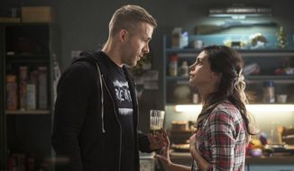 "This image released by Twentieth Century Fox shows Ryan Reyonlds, left, and Morena Baccarin in a scene from the film, ""Deadpool."" (Joe Lederer/Twentieth Century Fox Film Corp. via AP)"