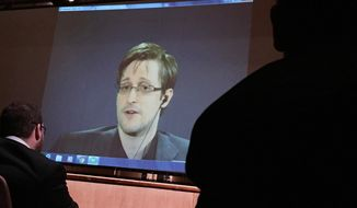 Former National Security Agency contractor Edward Snowden, center speaks via video conference to people in the Johns Hopkins University auditorium, Wednesday, Feb. 17, 2016, in Baltimore.  (AP Photo/Juliet Linderman)