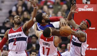 Washington Wizards guards John Wall (2), Garrett Temple (17) and Bradley Beal (3) combine to defend Detroit Pistons center Andre Drummond during the first half of an NBA basketball game Friday, Feb. 19, 2016, in Washington. (AP Photo/Alex Brandon)