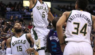 Milwaukee Bucks guard Michael Carter-Williams, center, gets a slam dunk against the Charlotte Hornets during the second half of an NBA basketball game Friday, Feb. 19, 2016, in Milwaukee. (AP Photo/Darren Hauck)