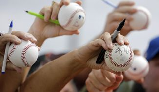 Fans hold out baseballs in hopes of getting an autograph following the New York Mets' spring training baseball practice Saturday, Feb. 20, 2016, in Port St. Lucie, Fla. (AP Photo/Jeff Roberson)