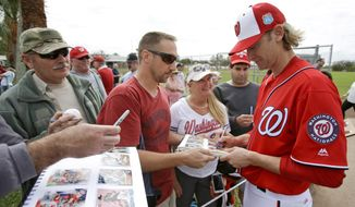 Bronson Arroyo, right, signs autographs for fans during a spring training baseball workout, Saturday, Feb. 20, 2016, in Viera, Fla. (AP Photo/John Raoux)