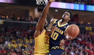 Michigan guard Derrick Walton Jr. (10) goes to the basket as he is fouled by Maryland forward Damonte Dodd (35) during the first half of an NCAA college basketball game, Sunday, Feb. 21, 2016, in College Park, Md. (AP Photo/Nick Wass)